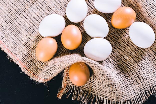 Huevos sobre mantel sobre fondo negro