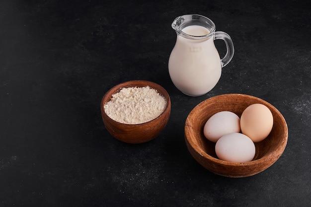 Huevos en una taza de madera con leche y harina alrededor.