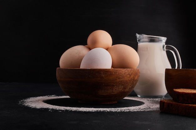 Huevos en una taza de madera con un tarro de leche a un lado.