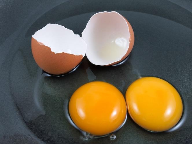 Huevos y cáscara agrietados en una cacerola negra