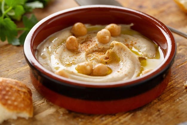 Hummus clásico oriental recién hecho servido en un tazón sobre la mesa.