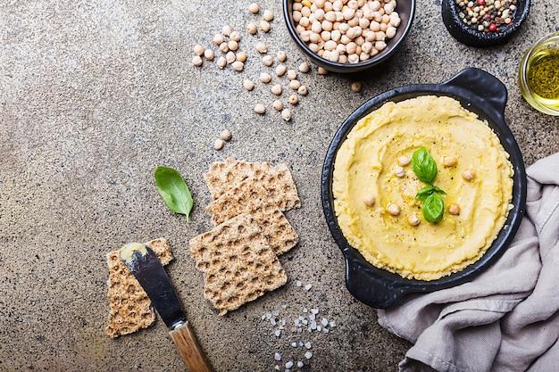 Hummus cremoso casero saludable con aceite de oliva sobre la superficie de piedra, vista superior