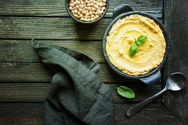 Hummus cremoso casero saludable sobre superficie de madera rústica, vista superior