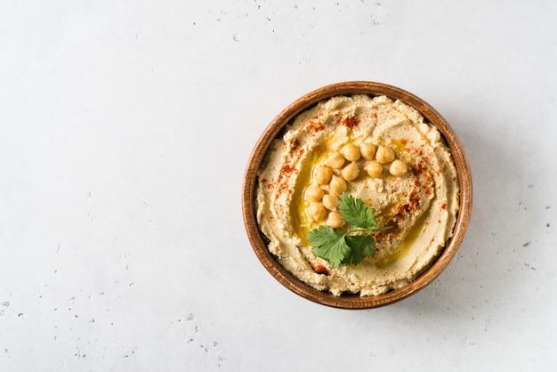Hummus dip con garbanzo y perejil en placa de madera sobre fondo blanco