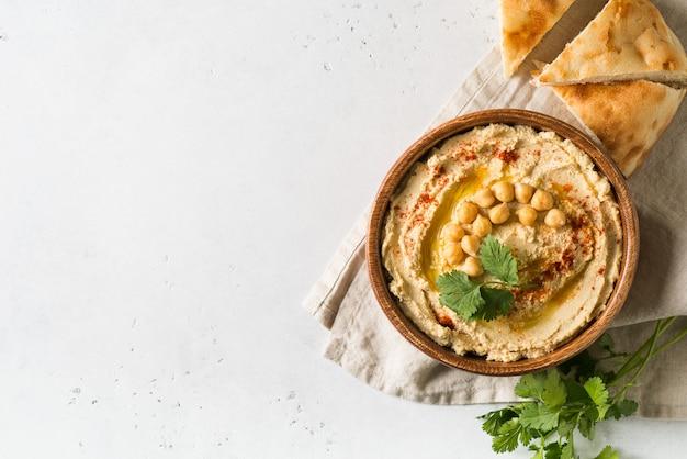 Hummus dip con garbanzo, pita y perejil en placa de madera sobre fondo blanco