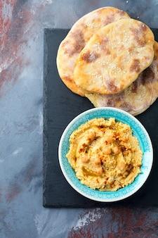 Hummus, garbanzos, con especias y pita, bizcocho plano en un plato sobre un fondo de piedra gris.