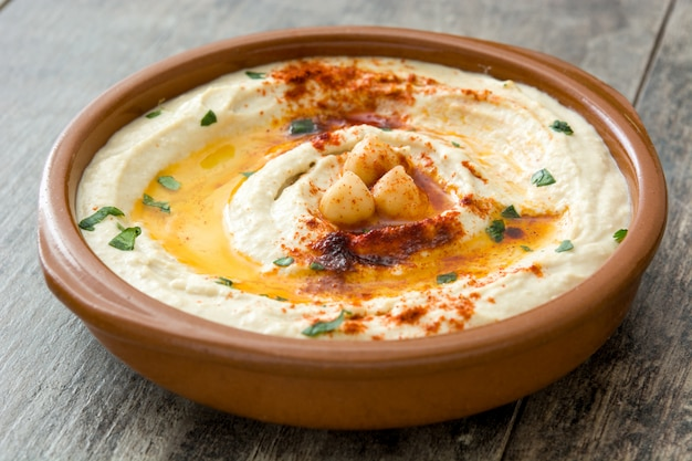 Hummus de garbanzos en un recipiente en la mesa de madera.