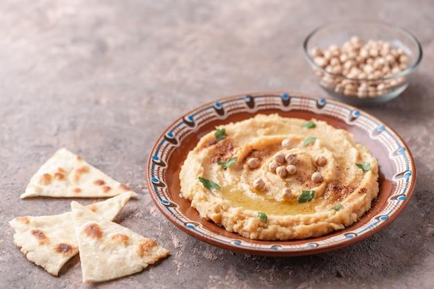Hummus en plato de arcilla marrón