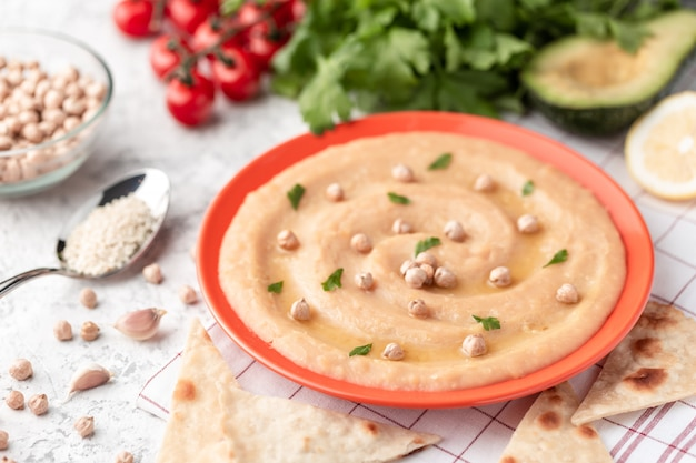 Hummus en un plato de naranja. sobre la mesa blanca hay verduras, verduras, trozos triangulares de pita.