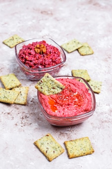 Hummus de remolacha con galletas saladas en superficie clara