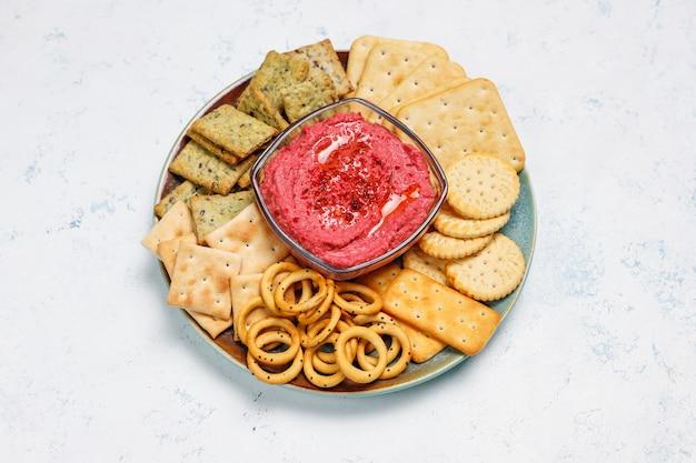 Hummus de remolacha en tabla de cortar con galletas saladas en superficie clara