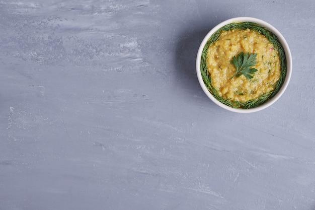 Hummus en una taza blanca con hierbas.