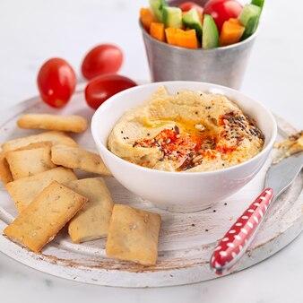 Hummus y verduras frescas merienda plato con galletas sobre un fondo claro. bocadillos saludables, dieta, concepto de comida.