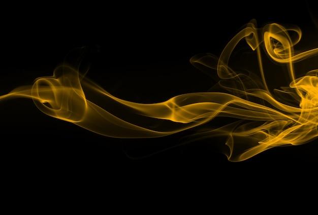 Humo amarillo abstracto en fondo negro. diseño de fuego
