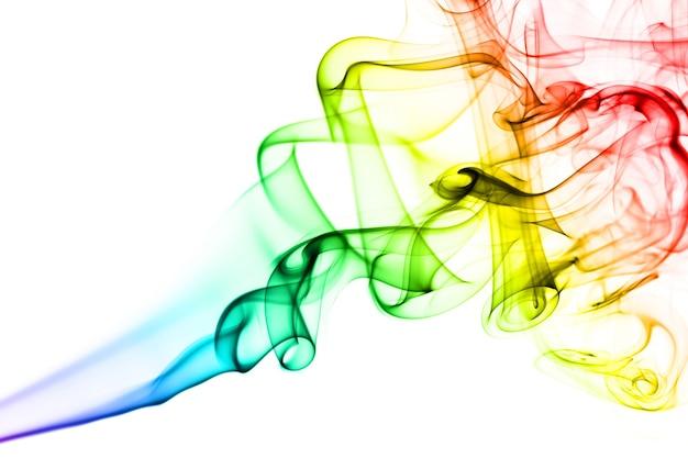Humo de arco iris sobre fondo blanco. el humo va de abajo hacia arriba. espirales de humo más cerca de la parte superior de la foto.