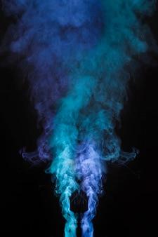 Humo azul claro y oscuro que sopla contra el fondo oscuro