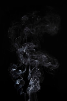 El humo blanco abstracto remolina en fondo negro