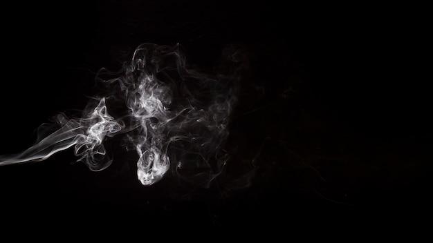 El humo blanco abstracto remolina sobre el fondo negro
