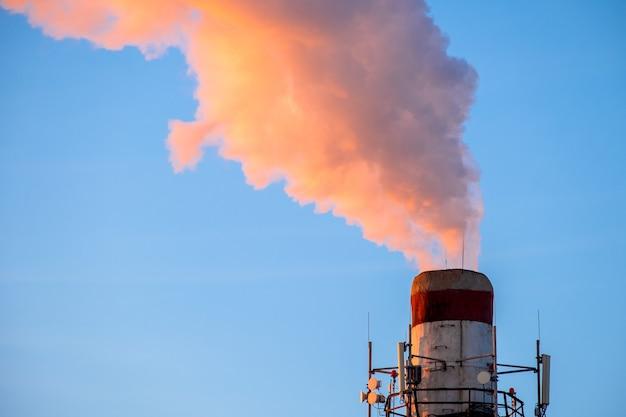 Humo de color naranja brillante y vapor de una alta chimenea de una planta de energía contra un cielo azul brillante