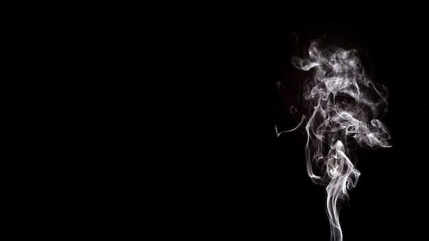El humo forma el movimiento sobre un fondo negro con espacio de copia para escribir el texto