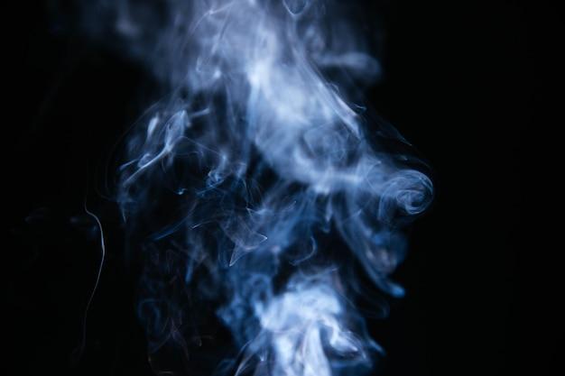 Humo ondulado azul sobre fondo negro