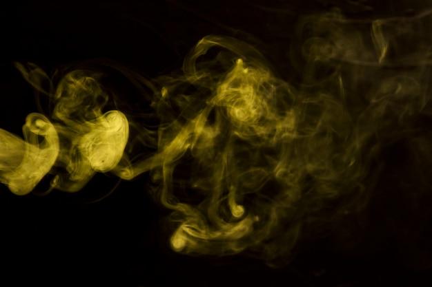 Humo que sopla amarillo abstracto en fondo negro