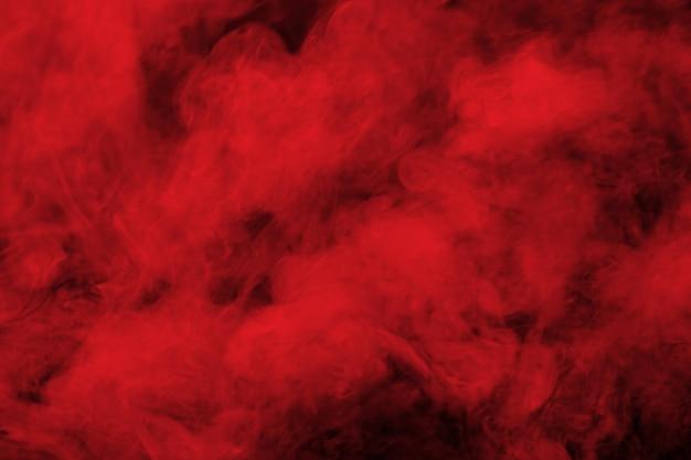 Humo rojo abstracto en fondo negro.