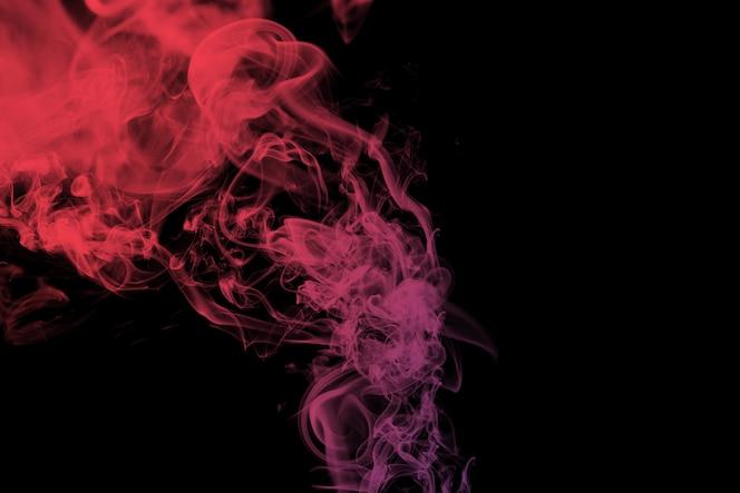 Humo rojo sobre fondo negro abstracto