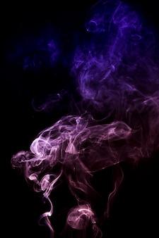 Humo rosado y azul abstracto extendido sobre fondo negro