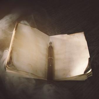 Humo sobre cuaderno antiguo y pluma de tinta