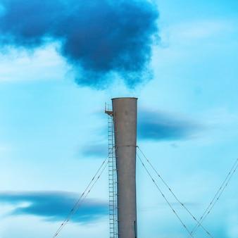 Humo tóxico negro industrial de la planta de energía de carbón en el cielo azul
