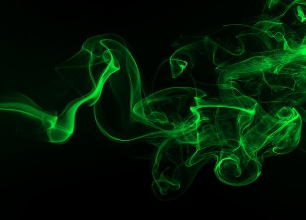 Humo verde abstracto en el fondo negro, concepto de la oscuridad