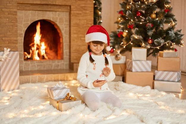 Humor navideño. niño lindo que sostiene el teléfono en las manos, consigue un teléfono inteligente como regalo de navidad, sentado en el piso sobre una alfombra suave cerca de las cajas de regalo y la chimenea, viste un sombrero festivo de santa claus.