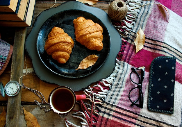 Humor de otoño composición de desayuno francés taza de té y cruasanes