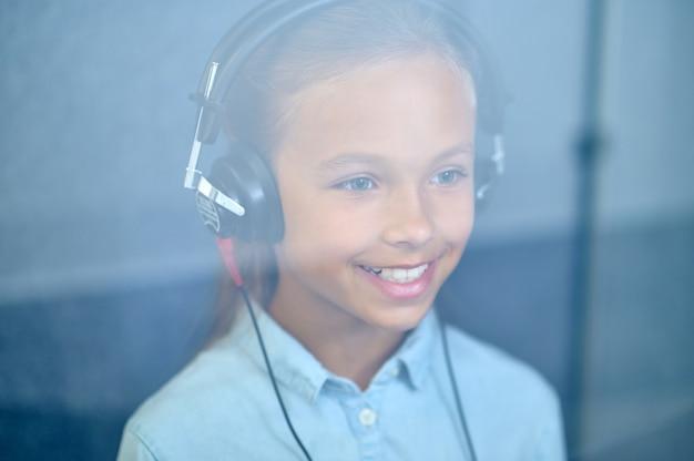 Humor positivo. feliz linda joven con audífonos detrás de un vidrio en la clínica médica en estado de ánimo optimista