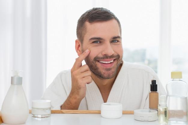 Humor positivo. hombre agradable encantado tocando su rostro mientras aplica la crema facial