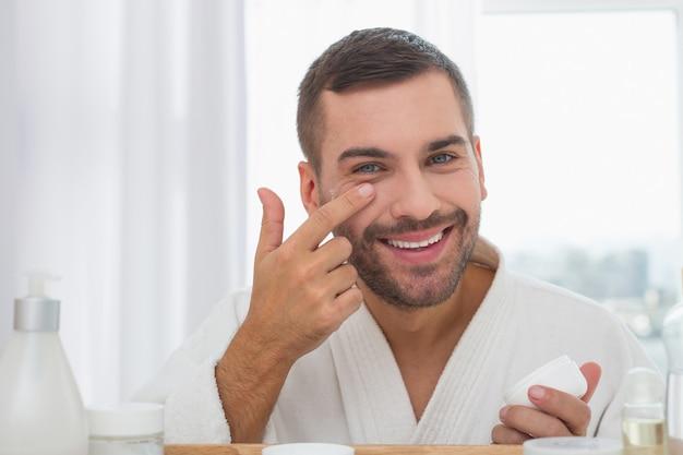 Humor positivo. hombre alegre encantado sonriendo mientras aplica la crema facial