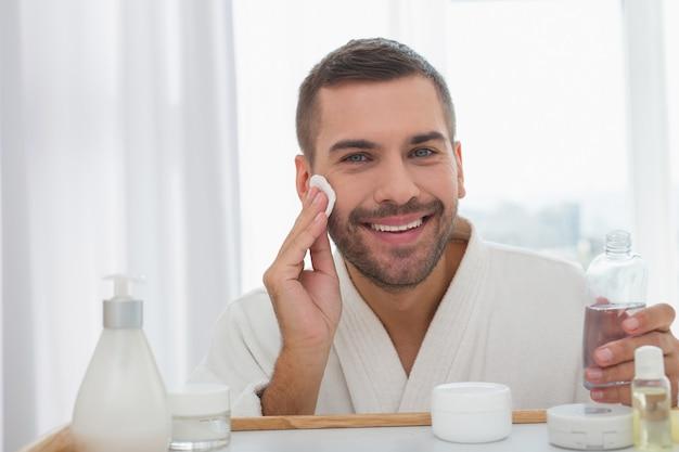 Humor positivo. hombre feliz alegre sonriendo mientras limpia su cara