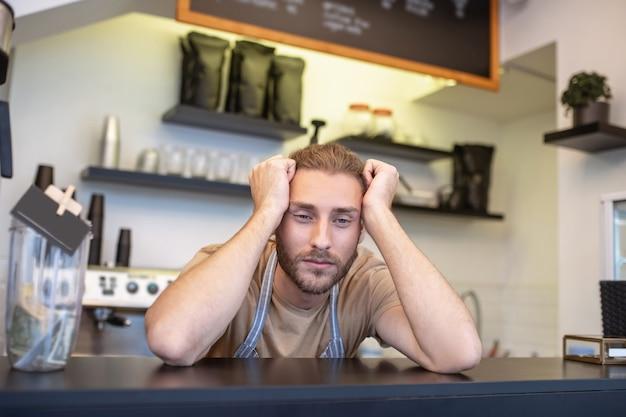 Humor triste. hombre barbudo joven aburrido en delantal de pie detrás de barra de bar en estado de ánimo triste