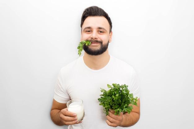 Hungru y divertido joven está parado y posa. él mira a la cámara. el chico sostiene un vaso de kéfir y un manojo de perejil en las manos. también hay alguna parte de planta verde en su boca. aislado en blanco