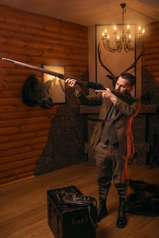 Hunter man apunta del rifle de caza antiguo