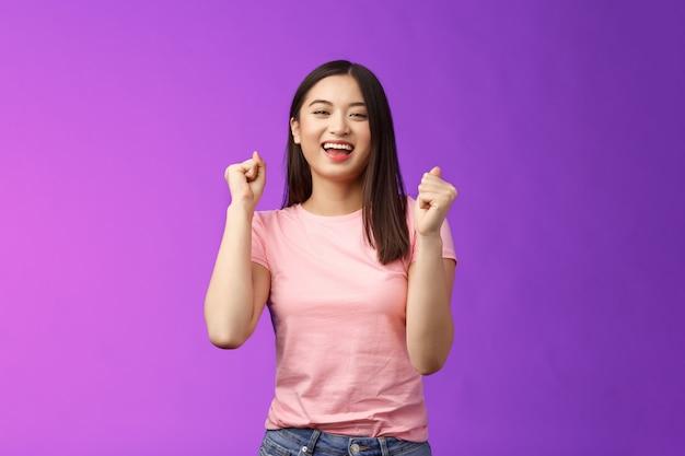 ¡hurra victoria afortunada! la chica asiática atractiva alegre hace la bomba de puño, el baile celebra la victoria, se para el fondo púrpura alegre, logra excelentes noticias sonriendo alegremente, mueve la música rítmica.