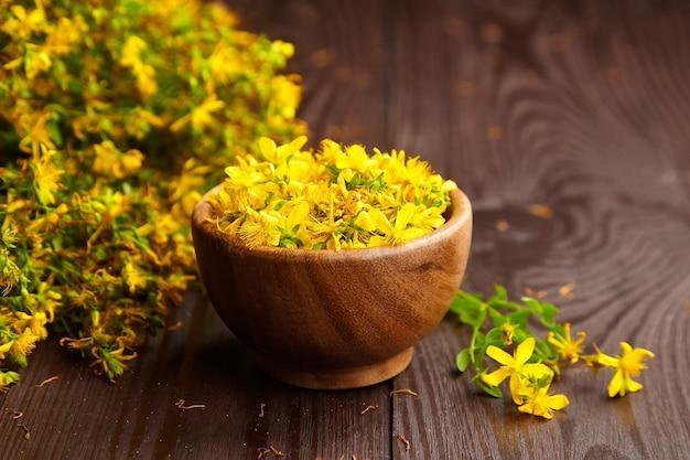 Hypericum perforatum o st johns wort capullos de flores en un tazón de madera