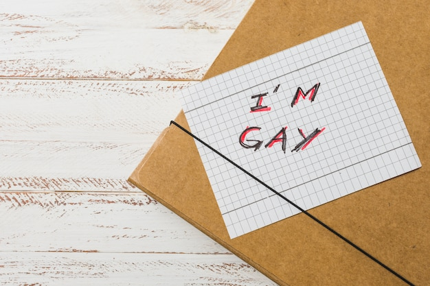 I inscripción gay en papel contra caso de documento.