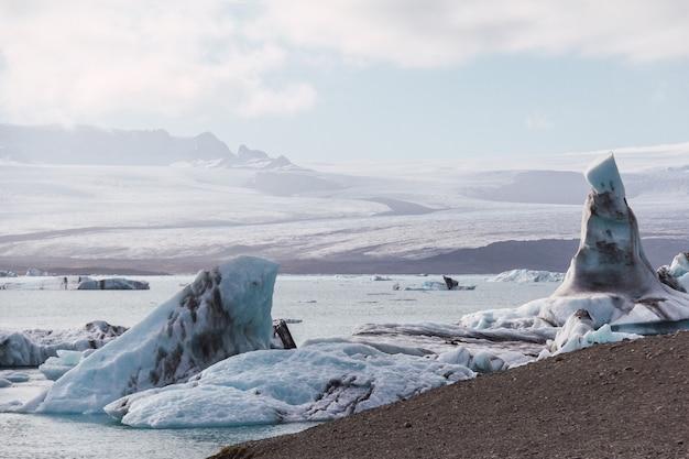 Icebergs en la laguna, islandia, parte del parque nacional glaciar. el pico más alto de islandia iluminado por el sol