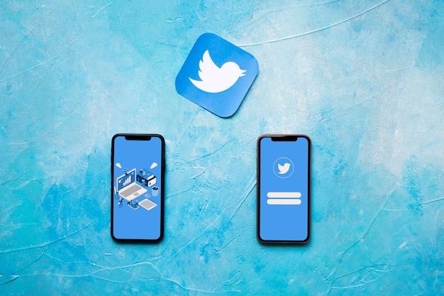 Icono de la aplicación de twitter y dos teléfonos celulares en la pared pintada de azul
