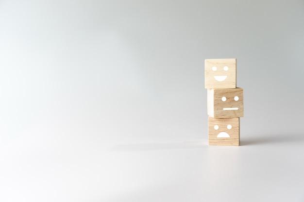 Icono de cara y carro de sonrisa en cubo de madera. persona optimista o personas que se sienten dentro y calificación de servicio al comprar, concepto de satisfacción.