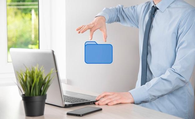 Icono de carpeta de mano. el sistema de gestión de documentos o la configuración de dms por un consultor de ti con una computadora moderna están buscando información de gestión y archivos corporativos.