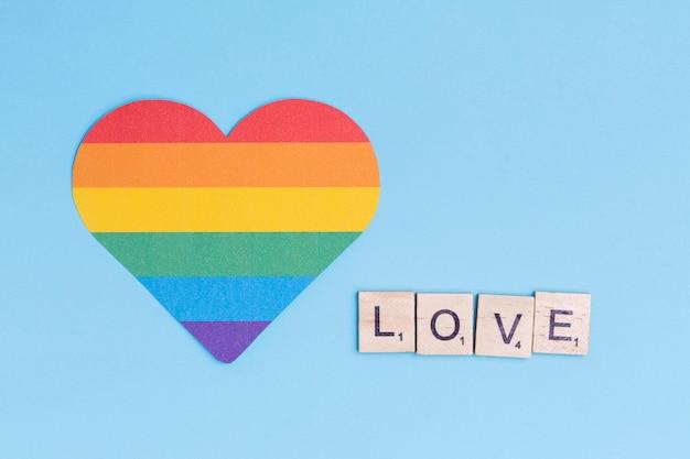 Icono de corazón lgbt y palabra amor en bloques de madera