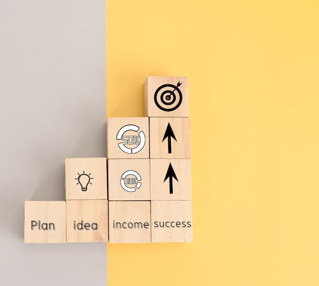 Icono de negocio en bloque de madera de plan, idea, ingresos y éxito
